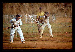 young men playing cricket