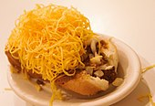 small oval white plate with cheese coney showing bun, hot dog, sauce, and shredded cheese