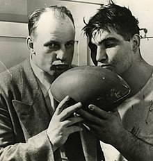 A picture of Bob Voigts and Alex Sarkisian kissing the game ball after the Rose Bowl in 1949