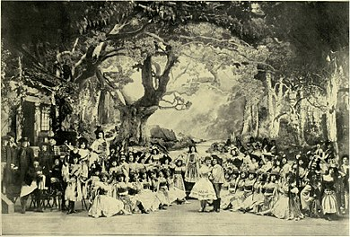 photograph of a large ballet troupe posed on a large stage with an elaborate woodland set