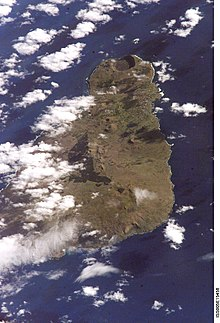 A colour photo from space showing a brownish triangular island in a dark blue sea; all partially obscured by white clouds especially on the left.