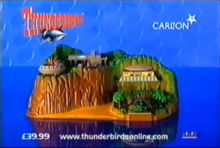 "Scale, toy model of a tropical island, with stationary, futuristic air- and spacecraft and ""Thunderbirds"" and ""Carlton"" titles"