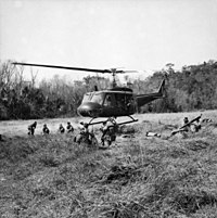 A black and white image of an Australian Iroquois helicopter inserting troops into a Landing Zone during the battle