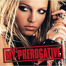 "The face of a blonde woman. She is holding a microphone in her hand next to her head, while looking towards the left side of the picture. She is wearing different rings in her fingers. She is wearing a black vest. On the lower part of the image, the words ""My Prerogative"" are written in red capital letters inside a box of the same color."
