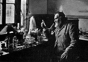 A bearded old man holding up a test tube. He is sitting at a table by a window. The table is covered with many small bottles and test tubes.