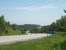 """A photo of a four-lane divided highway on a sunny day."""