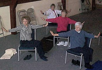 Seniors practicing chair yoga