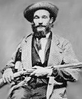 Black and white image of a bearded man with a hat, wearing a jacket over a suit and tie; he is seated and holding a rifle across his lap.