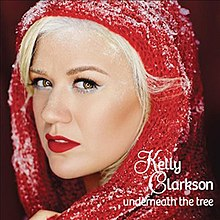 "A blonde woman whose head is wrapped in a red scarf and covered with snow, on the lower right, the wordmarks ""Kelly Clarkson"" and ""Underneath the Tree"" are printed in stylized ""Feel Script"" and ""Bree"" typefaces."