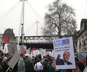 2011 London anti-cuts protest - A poster critical of health secretary Andrew Lansley for his plans perceived as including increased privatisation of the NHS.