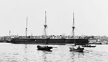 A large black warship sits in port with several small boats in the foreground.