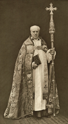 bald, clean-shaven white man in ecclesiastical robes, carrying as staff surmounted by a cross