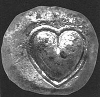 Ancient silver coin from Cyrene depicting a silphium seed or fruit.
