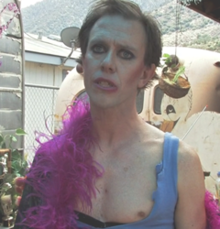 Sean Whalen in dim lighting, with heavy make-up around his eyes. He wears a light blue tank top with a pink scarf over it. His left nipple is exposed.