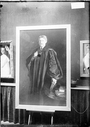 Frank W. Gunsaulus - Image of a framed portrait painting of Frank W. Gunsaulus wearing academic robes, by Louis Betts – displayed on an easel in front of a wall with other paintings in Chicago, Illinois.