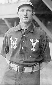 "A man wearing a dark baseball uniform with ornate ""N"" and ""Y"" over each breast and a white baseball cap"