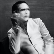 Image of a man wearing heavy make-up and a white jacket, who is sitting on a black chair and a grey-painted backdrop is visible behind him. The man's face is partially obscured by blurring, as is his right hand, which is being held upright.
