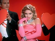 Madonna in a pink gown and jewels, surrounded by men in tuxedos
