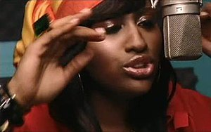 Need U Bad - Sullivan in a scene from the music video, singing into a recording studio microphone.