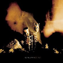 Two skeleton dolls wearing crowns stand in a darkened room with rocks Orange glows are seen through the image