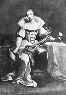 An image of Bridget Paston, Edward Coke's first wife. She is sat next to a table covered in white cloth, on which she rests her arm, and is wearing a white dress with a corset, a long skirt and a wide ruff around the neck and shoulders.