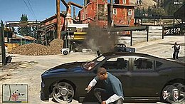 The player character crouched behind a vehicle while in combat. The head-up display elements are visible on-screen.