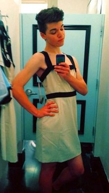 Teenaged, white, trans girl with dark hair wearing a white dress and posing in front of a mirror, taking a photograph of herself using a camera phone.