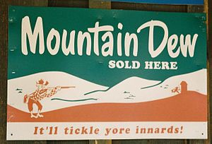 "Mountain Dew - 1950s Mountain Dew advertisement sign in Tonto, Arizona showing the  cartoon character ""Willy the Hillbilly""."