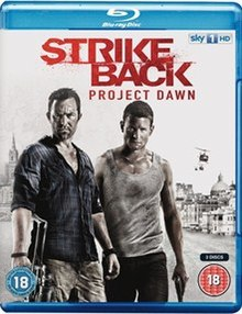 "A blu-ray disc cover with a white/greying background and the title ""Strike Back Project Dawn"" in red letters on the top. Below it are two men. The man on the left is stubbly with a blue shirt and holding a machine gun in his right hand. The man on the right is wearing a dirty vest and holding a pistol in his left hand. Behind them is a city skyline with three helicopters flying overhead."