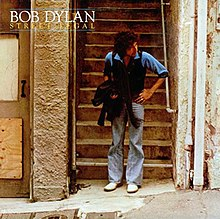 Dylan standing, slightly bent at the waist, in front of a stairwell