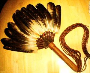 Gourd Dance - A Warriors (Male) Gourd Dance Eagle Fan. This Gourd Dance fan is made from immature bald eagle feathers.  The handle of this fan was made from the branch of a tree struck by lightning, and the handle of the fan has been stitched, bound, and fringed with bison hide.