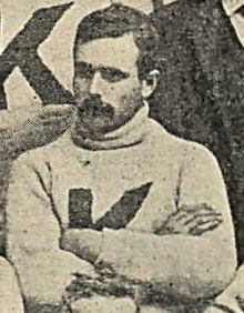 A man with a mustache is looking down to his right and wearing a sweater with a big K on it.