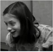 A black and white frame taken from a video of Genie, who is enthusiastically smiling, taken from several feet away. It shows her from the chest up, and Genie is facing slightly to the right of the camera.
