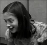 A black and white frame taken from a video of Genie, who is enthusiastically smiling. It shows her from the chest up, taken from several feet away while Genie is facing slightly to the right of the camera.