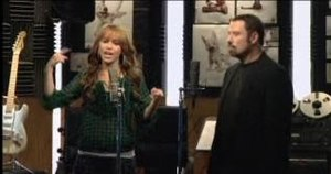 """I Thought I Lost You - Cyrus and Travolta performing in a recording studio in the """"I Thought I Lost You"""" music video."""