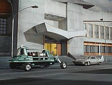 Two very different vehicles are parked at the side of a street in front of the entrance to a grey concrete building. The vehicle on the left is viridian green and of an eccentric design, with a turbine engine positioned behind a cockpit to seat the driver and passengers. The vehicle on the right is a car of a more standard appearance and grey in colour, although it is fitted with tail fins at the rear.