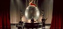The stage concert house, with red curtains on the side and grey ones in the background. Atop a scenographic Earth globe lies a woman in a red dress, while below it three men in suits play drums, bass and guitar.