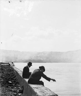 Reclamation of Wellington Harbour - Two men fishing off the reclamations at Te Aro, in the vicinity of Cable Street, Wellington. Photograph taken circa. 1910.