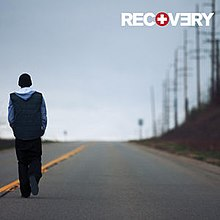 The cover features Eminem walking down the road under clear blue sky. On top-left corner, in bold and capitalised format, the title RECOVERY appears.