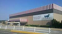 "A square building with red and white vertical striping along the roof. A banner on the front shows Rosecroft's logo and the statement ""Welcome Back Racing Fans!"""