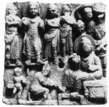 Ancient relief showing the Buddha standing surrounded by several monks in the upper part, with one monk hurling a boulder at the far right. Below a man is kneeling and holding the feet of the Buddha, while a child is standing behind the kneeling man, holding some object.