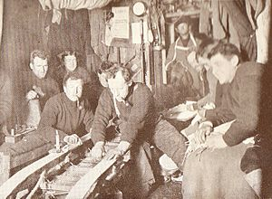 Ernest Joyce - Inside the Cape Royds Hut, winter 1908. Joyce is on the right, foreground. Also included in the picture are Shackleton (left background), Adams (smoking curved pipe), and Wild (working on the sledge).