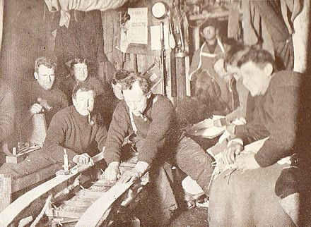 Inside the Cape Royds Hut, winter 1908. Included in the picture are Shackleton (left background), Armytage (Standing background), Adams (smoking curved pipe), Wild (working on the sledge) and Joyce (extreme right, foreground). A poster advertising ladies' corsets hangs on the wall. CapeRoyds1908.jpg