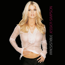 "A blonde woman is standing in front of a black background. She is looking directly to the camera while placing her hands in front of her hips. The woman wears a thin blouse and black jeans. At her left side, the word ""Irresistible"" is written vertically in white capital font, and ""Jessica Simpson"" in pink capital letters."