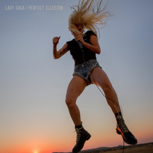Gaga singing into a microphone while jumping. She wears a shorts and t-shirt with her hair in a ponytail. Behind her, sunset can be seen.