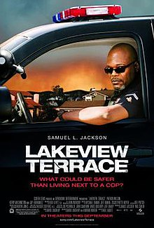 a bald police officer with sunglasses in a car looks toward the viewer. Below him shows the actor who plays him, the title, statement, production credits and release date.