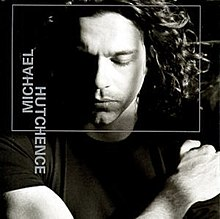 A black-and-white photo of Hutchence lying down with a thin grey square superimposed around his face and his name written vertically on the left-hand side in grey.