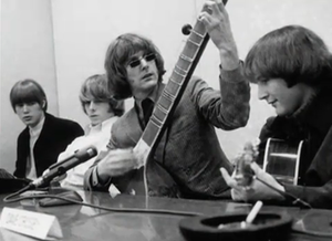 "Eight Miles High - The Byrds at the ""Eight Miles High"" press conference in March 1966, posing with a sitar in order to illustrate the Indian influences present in the song."