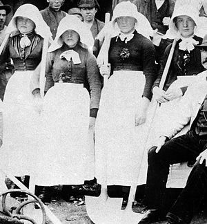 Four women wearing dark heavy clothing, bright white aprons, and long white bonnets entirely covering the sides of their heads and protruding forwards over their faces