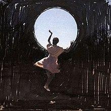 Женщина танцует на черном фоне, держа в руках круг неба.